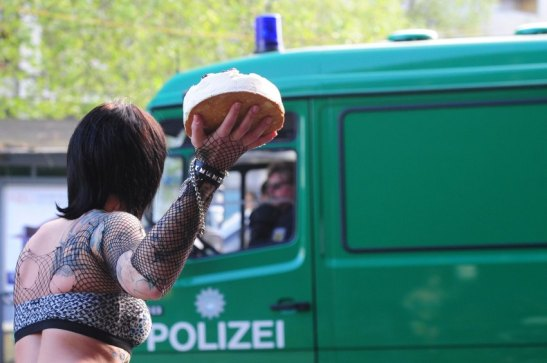TOPSHOTS A woman pretends to throw a cake towards a police car during May Day celebrations on May 1, 2011 in Berlin. The international day of the worker has for the past two decades been accompanied in German cities by sporadic street violence and pitched battles between far-right skinheads, anti-fascist groups and police.     TOPSHOTS / AFP PHOTO / JOHANNES EISELE