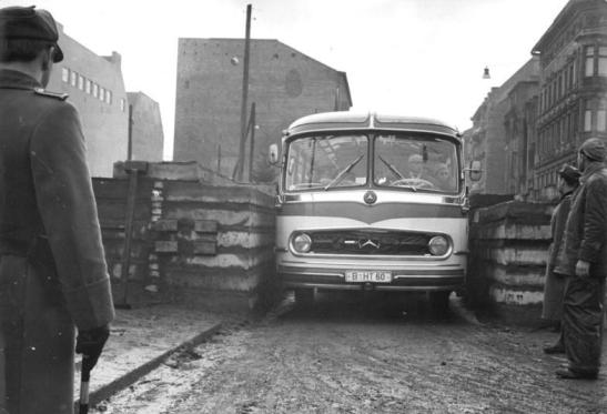The construction of Berlin Wall at Checkpoint Charlie in 1961 - the bus is passing  from East Berlin (Mitte) to West Berlin (Kreuzberg) (photo: Stöhr, Bundesarchiv_Bild_183-88574-000)