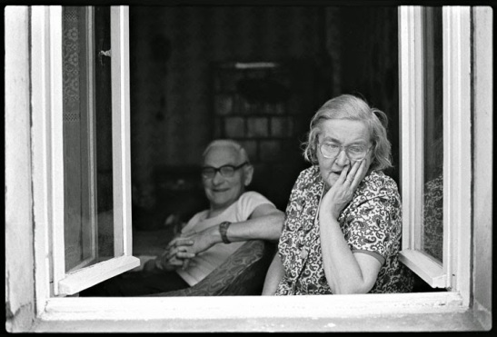 A couple at the window: what kind of life do they have behind them and what kind of future before them?