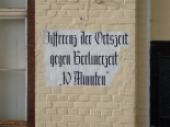 "An original sign painted on the wall of a railway station somewhere in Germany, informing passengers about the necessary time adjustment in reference to the ""Berliner Zeit""."