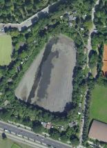 The outline of the old Rütt-Arena still used as a rain-water basin and surrounded by small allotments (image from Google Maps).