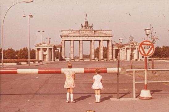 two girls in front of the ddr schlagbaum at brandebrug gate
