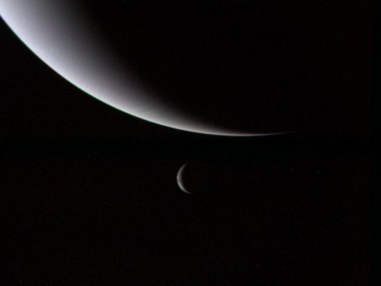 Neptune and its largest moon, Triton, photographed by Voyager 2 space prob.